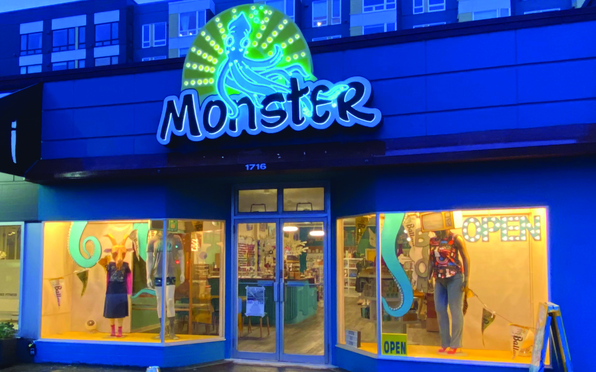 Photo of exterior of a storefront in the evening with the Monster logo