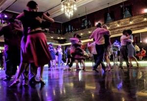 People dancing in ballroom space.