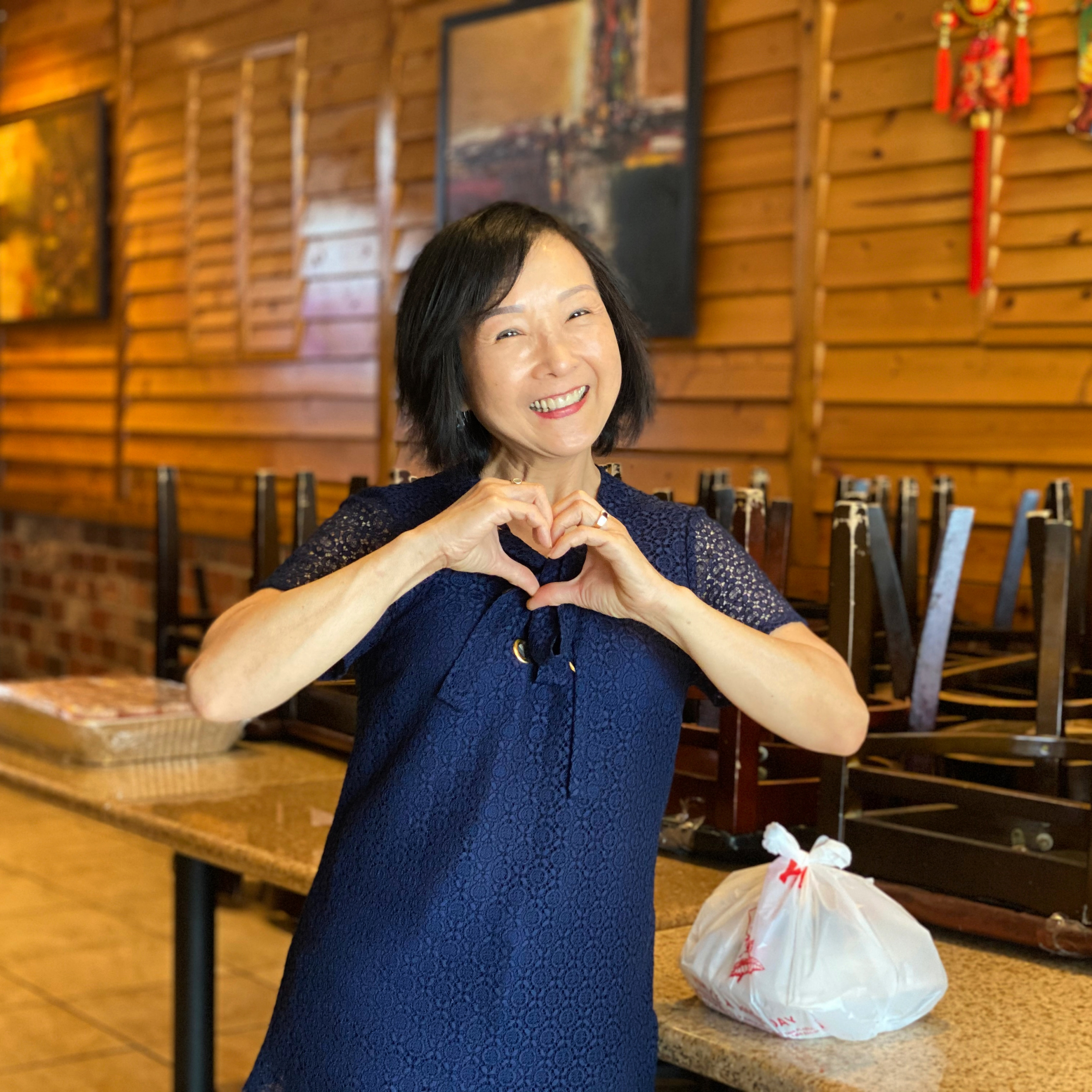 Co-owner Trinh Ong makes a heart shape with her hands, standing next to a takeout order in her restaurant.