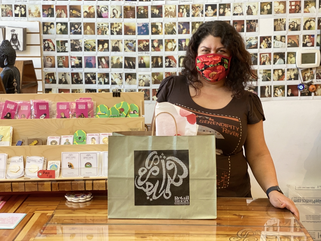 Image of Retail Therapy owner, Wazhma Samizay, wearing a facemask standing behind the counter of her store. There is a bag with a gift on the counter in front of her.