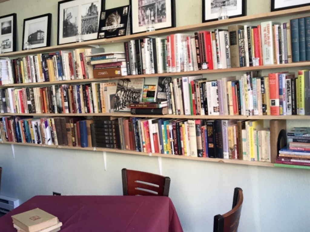 Picture of books on shelves with a table and chairs in the foreground.