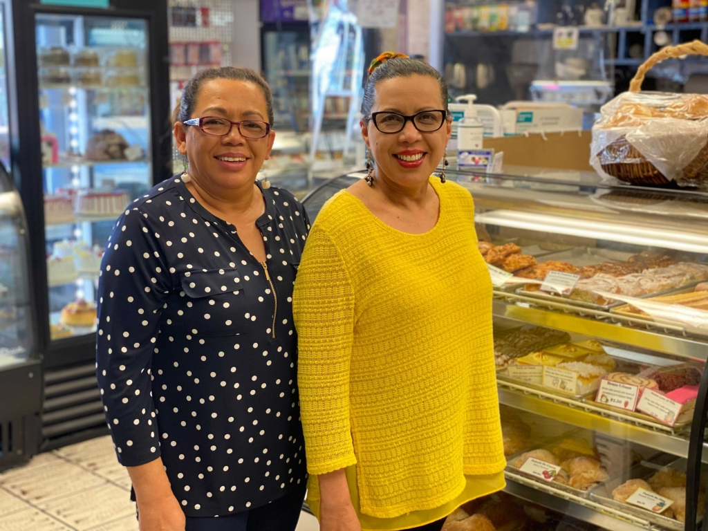 Sisters Aminta Elgin and Ana Castro standing in front of one of their pastry cases.