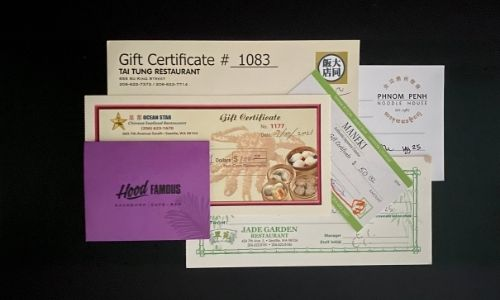 Various gift certificates arranged on a black background